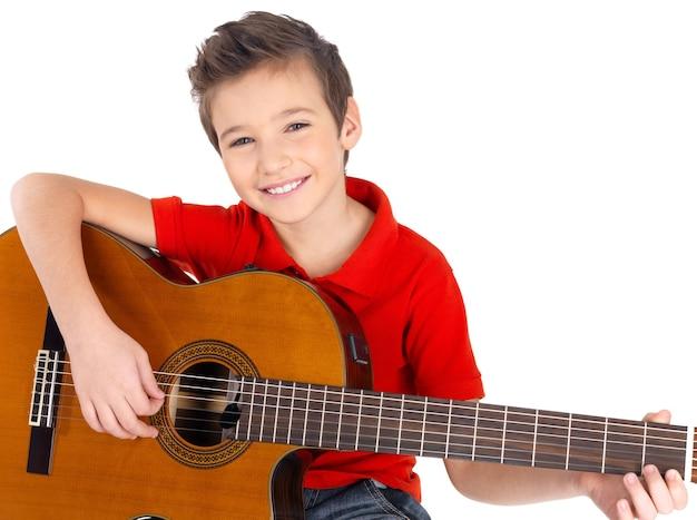 Hübscher glücklicher junge spielt auf der auf weiß isolierten akustikgitarre