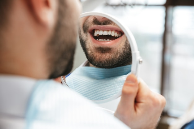 Hübscher glücklicher junger mann, der im medizinischen zahnarztzentrum sitzt und spiegel betrachtet
