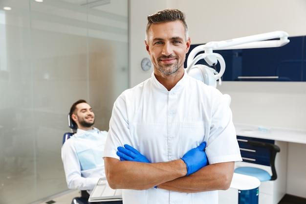 Hübscher glücklicher junger mannarzt im medizinischen zahnarztzentrum
