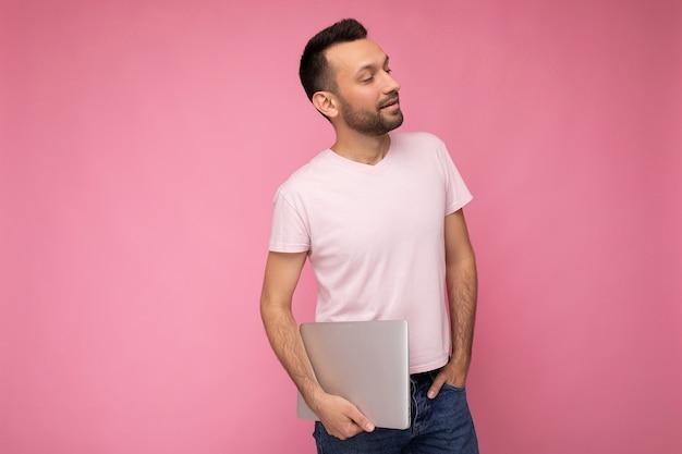 Hübscher glücklicher junger unrasierter mann, der laptop-computer hält, der im t-shirt auf lokalisiertem rosa hintergrund zur seite schaut.