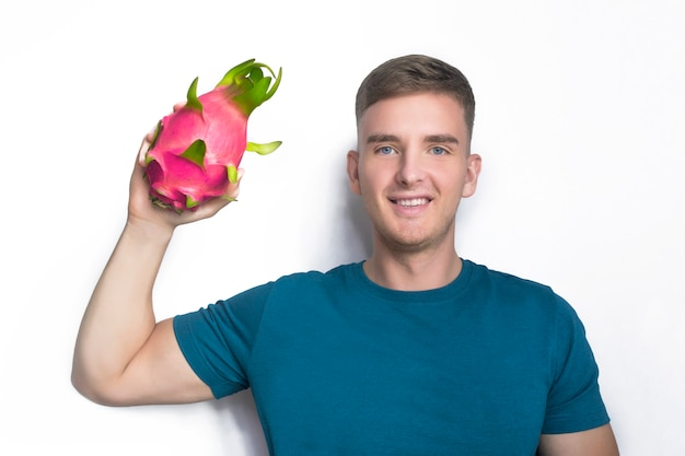 Hübscher glücklicher kerl, junger mann, der frische reife frucht, rote tropische pitaya, pitahaya, drachenfrucht oder kaktuslächeln lokalisiert auf weiß hält. gesunde ernährung, essen, vegan oder vegetarisch. liebesfruchtkonzept