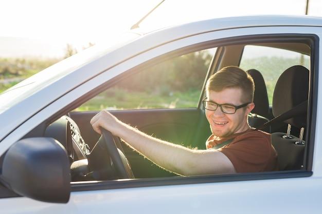 Hübscher glücklicher lachender junger mann fährt ein auto.