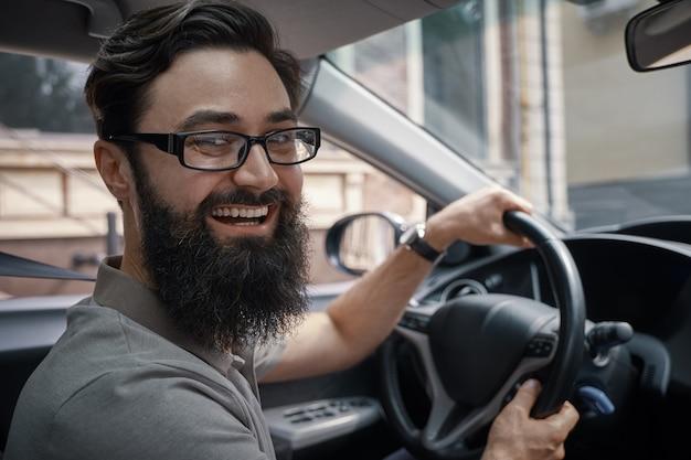 Hübscher, glücklicher mann, der das auto fährt