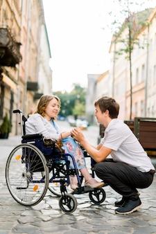 Hübscher glücklicher mann, der lächelt und hand seiner schönen geliebten blonden behinderten frau im rollstuhl hält, während sie zusammen auf der straße der alten stadt gehen