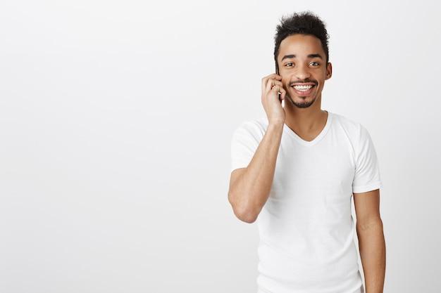 Hübscher glücklicher schwarzer mann, der lächelt und auf handy spricht