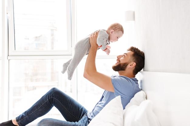 Hübscher glücklicher vatervater des jungen mannes, der spaß mit seinem kleinen baby hat