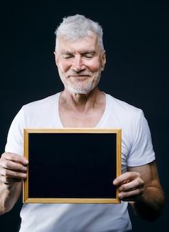 Hübscher grauhaariger älterer mann mit brett in den händen sport- und gesundheitskonzept