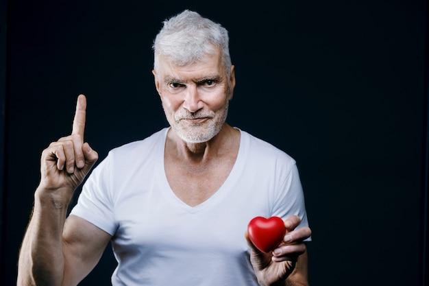 Hübscher grauhaariger älterer mann mit herz in den händen sport- und gesundheitskonzept