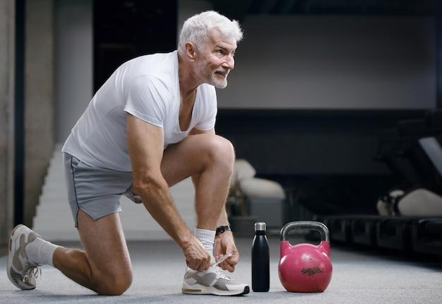 Hübscher grauhaariger älterer mann mit kettlebell-gewicht