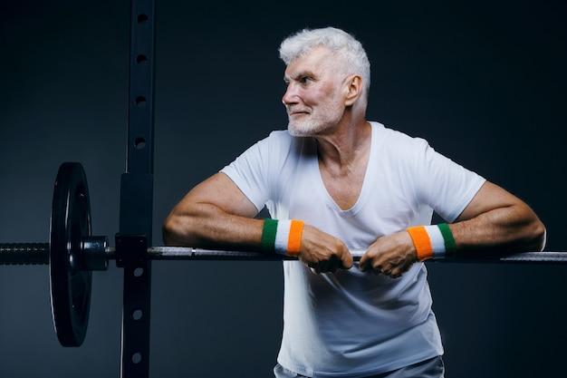 Hübscher grauhaariger älterer mann mit stirnband und armbändern sport- und gesundheitskonzept