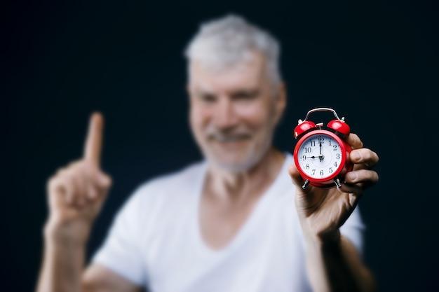 Hübscher grauhaariger älterer mann mit wecker in den händen sport- und gesundheitskonzept