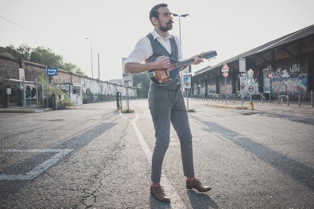 Hübscher großer schnurrbarthippie-mann, der mandoline spielt