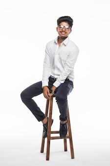 Hübscher gut aussehender indischer mann, der auf einem stuhl sitzt und sich entspannt, lokalisiert für weiße wand