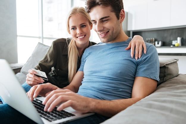 Hübscher gutaussehender mann und frau, die laptop-computer verwendet