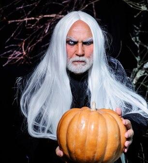 Hübscher halloween-mann mit kürbis in der hand. teufel mann. mann im hexenkostüm bereit zur halloween-party.