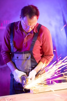 Hübscher handwerker mittleren alters in jumpsuit-schutzbrille und handschuhen, die metall mit funken in farbigen hellen metallarbeiten schleifen