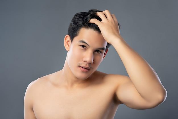 Hübscher hemdloser asiatischer mann, der sein haar berührt