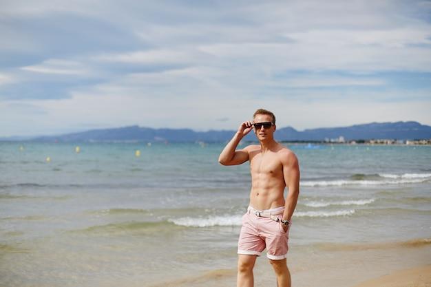 Hübscher hemdloser athletischer junger mann, der am strand durch die wasserlinie geht. junger muskulöser mann mit perfektem körper in shorts und sonnenbrille, die durch die seeküste gehen. reisemode. sportlicher lebensstil