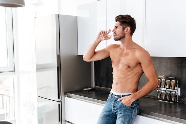 Hübscher hemdloser junger mann, der wasser auf der küche trinkt
