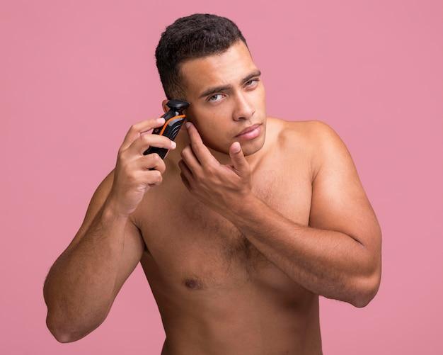 Hübscher hemdloser mann, der einen elektrischen rasierer benutzt