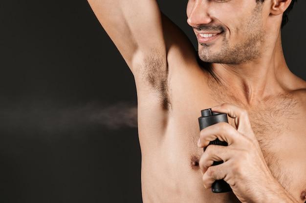 Hübscher hemdloser mann, der isoliert steht und deodorant auf seine achselhöhle sprüht