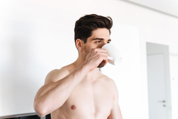 Hübscher hemdloser mann, der kaffee trinkt