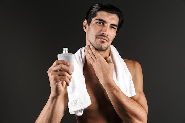 Hübscher hemdloser mann mit handtuch auf seinen schultern, die isoliert stehen und aftershave anwenden