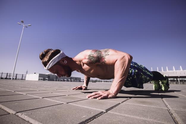 Hübscher hemdloser sportler, der wegschaut und an einem sonnigen tag im freien auf dem trainingsgelände push-up-übungen macht. sportlicher lebensstil.