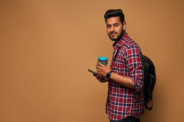 Hübscher hinduistischer mann, der mit kaffee zum mitnehmen und rucksack auf pastellfarbener wand nach vorne schaut