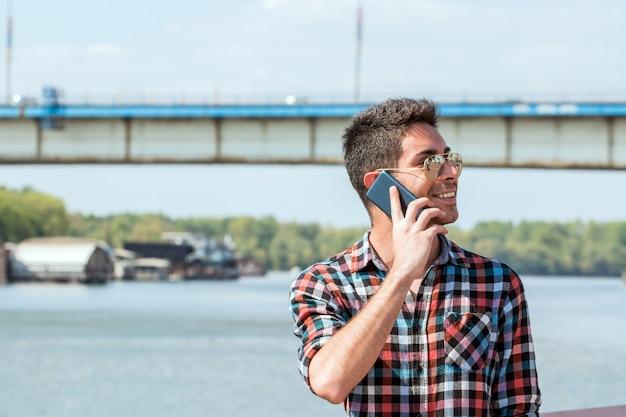 Hübscher hippie, der am telefon spricht.