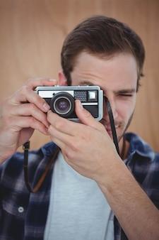 Hübscher hippie, der foto mit retro- kamera macht