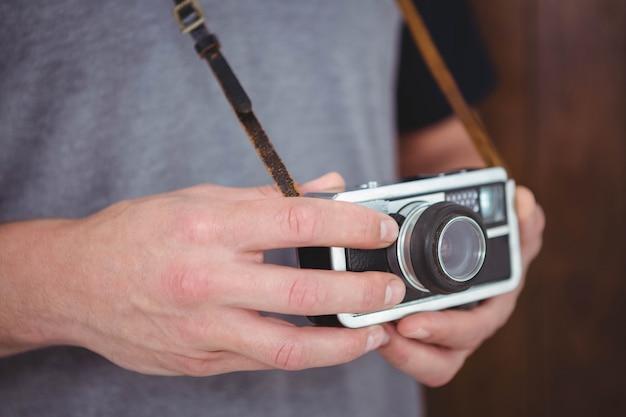 Hübscher hippie, der retro- kamera mit fokus auf händen hält