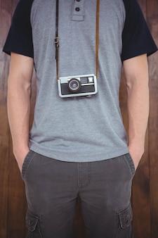 Hübscher hippie, der retro- kamera um hippie-hals hält