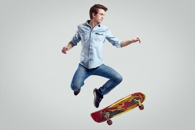 Hübscher hippie-mann in der jeansjacke, die den leichten schlag auf stilvollem skateboard tut