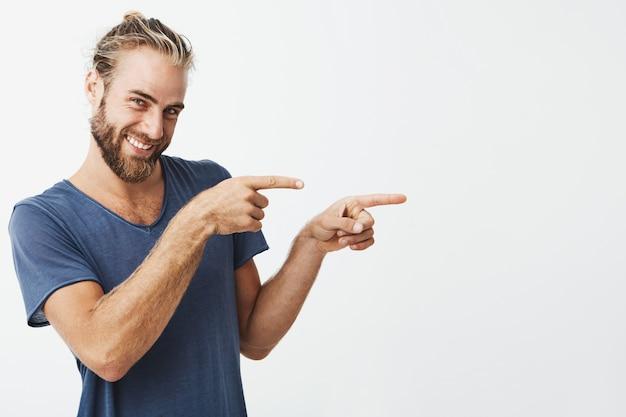 Hübscher hipster-mann, der mit den fingern auf copyspace zeigt