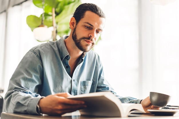 Hübscher hipster-mann, der sich entspannt, las das papierbucharbeitsstudium und das seitenmagazin betrachtend, während er auf stuhl im café und im restaurant sitzt
