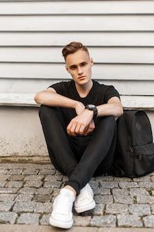 Hübscher hipster-mann in einem schwarzen hemd, in schwarzen jeans und in weißen schuhen mit einem rucksack, der nahe der wand sitzt.