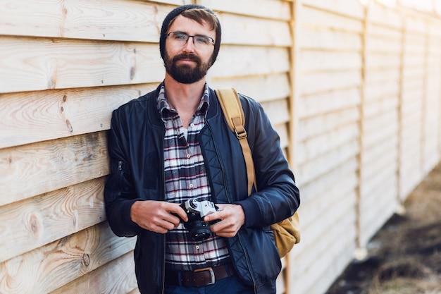 Hübscher hipster-mann mit bart, im stilvollen hut und in der brille, die mit retro-kamera in den händen aufwirft