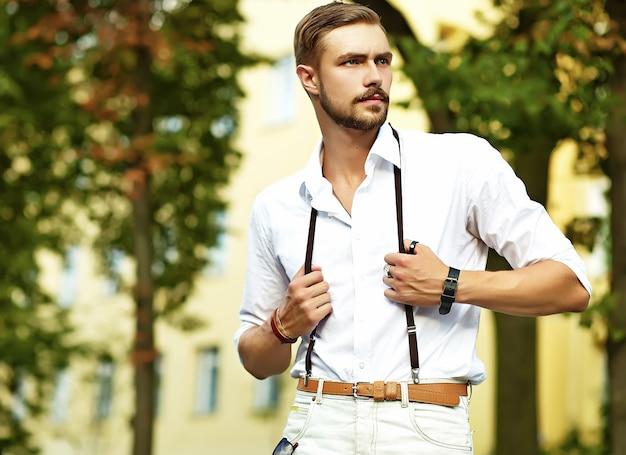 Hübscher hipster-modellmann in der stilvollen sommerkleidung, die aufwirft