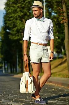 Hübscher hipster-modellmann in der stilvollen sommerkleidung, die im hut mit tasche aufwirft