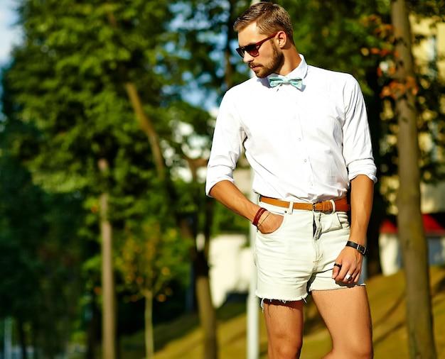 Hübscher hipster-modellmann in der stilvollen sommerkleidung, die in der sonnenbrille aufwirft