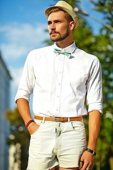 Hübscher hipster-modellmann in stilvoller sommerkleidung, die im hut aufwirft