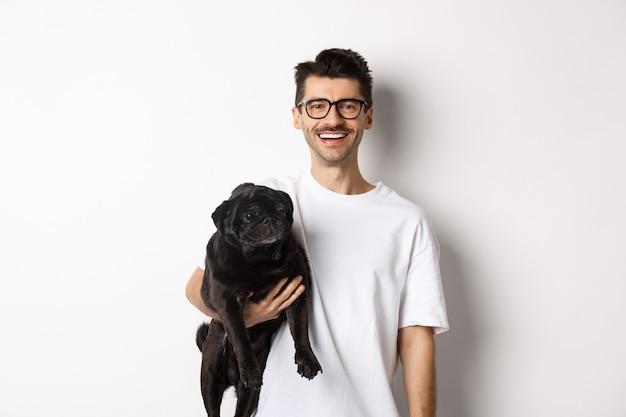 Hübscher hipster-typ, der seinen lustigen schwarzen mopshund hält, in die kamera lächelt und auf weißem hintergrund steht.