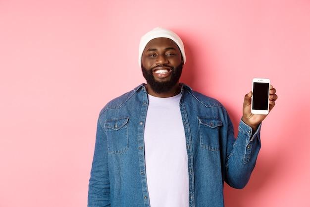 Hübscher hipster-typ in mütze und jeanshemd lächelt, zeigt handy-bildschirm mit glücklichem gesicht, stellt anwendung vor, steht auf rosafarbenem hintergrund