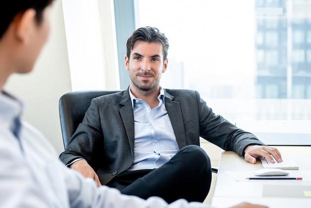 Hübscher hispanischer geschäftsmann als chef, der im büro sitzt