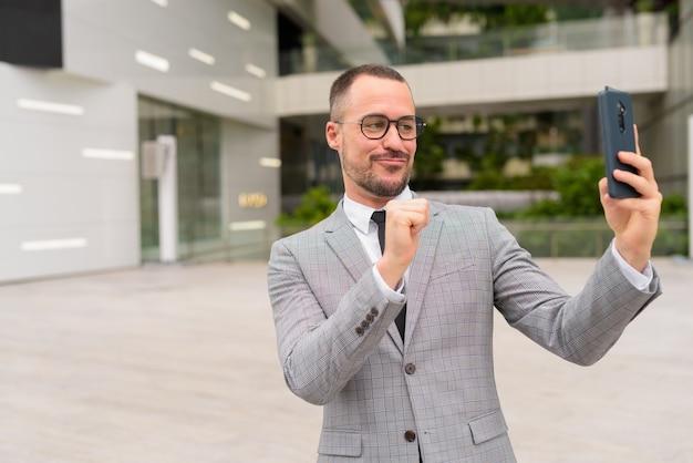 Hübscher hispanischer kahler bärtiger geschäftsmann, der selfie mit brille in der stadt nimmt