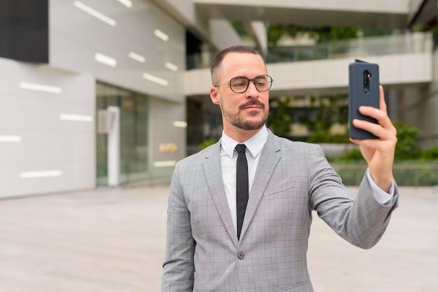 Hübscher hispanischer kahler bärtiger geschäftsmann, der selfie mit brillen in der stadt draußen nimmt