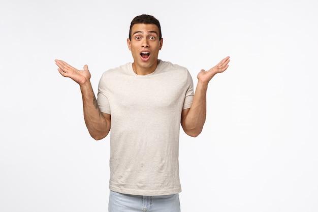 Hübscher hispanischer muscline machomann im weißen t-shirt, heben hände seitlich an