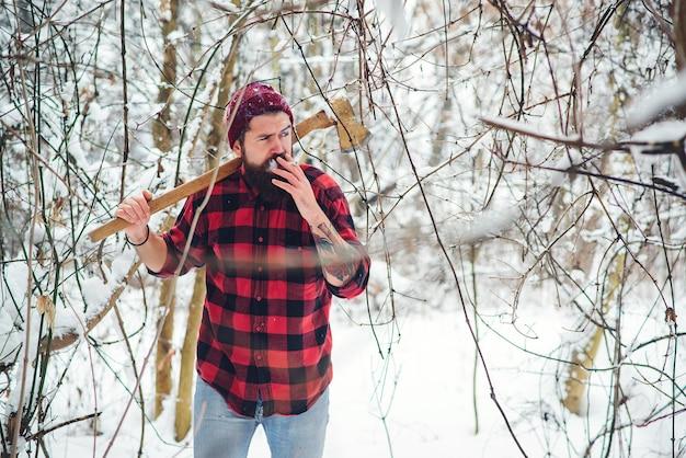 Hübscher holzfäller, der im winterwald raucht