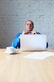Hübscher hübscher reifer mann, der bei tisch vor laptop sitzt und auf untergebenen hört